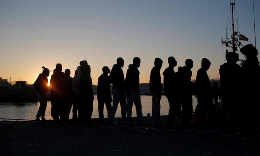 People line up for food after arriving on rescue boats