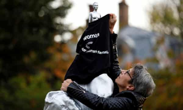 A protester covers the statue with a T-shirt.