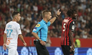 The referee, Clement Turpin, gestures as he halts the game after supporters shouted homophobic songs and brandished banners during the the match between Nice and Marseille.