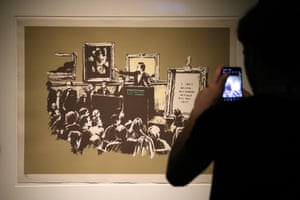 A visitor takes a photo at a preview of The Art Of Banksy exhibition in Sydney, Australia