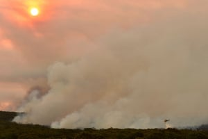 A helicopter drops water on to a large bushfire in Bargo, 150km south-west of Sydney. An unprecedented heatwave has fanned out-of-control bushfires, destroying homes and smothering huge areas with a toxic smoke