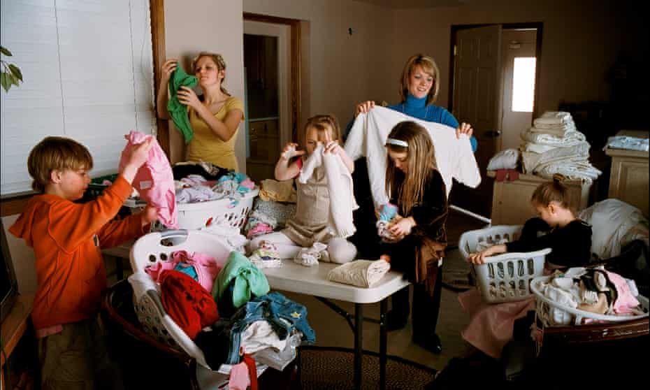 Valerie, one of three wives in a polygamist family living in the Salt Lake Valley, Utah, folds the laundry with the help of five children.