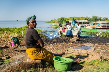 Women wait for fishermen to return with the catch, on the beach at Dunga village, near Kisumu, Kenya.