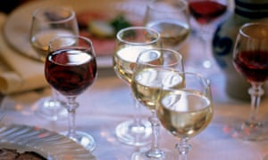 Glasses of red and white wine on a dinner table.