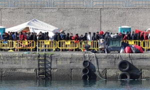 Migrants queue up to receive assistance at Arguineguín port in Gran Canaria on Sunday. The regional president said almost 2,200 people were being housed on the docks.
