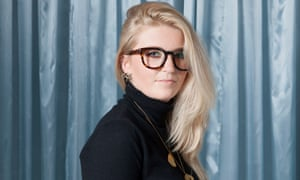 Kate Moyle with long blonde hair swept to one side and heavy-rimmed glasses