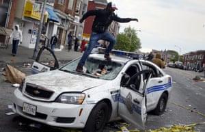 A demonstranci skoki na uszkodzonym pojeździe departament policji w Baltimore podczas starć w Baltimore.
