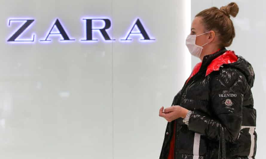 A woman in a medical mask walks past a Zara store in Moscow.