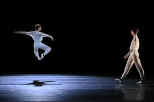 A male dancer leaps into the air as another looks on