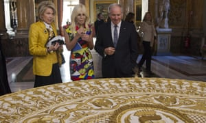 Christine Hearst Schwarzman, Donatella Versace and Stephen A Schwarzman admire a liturgical vestment of Pope Benedict XV.