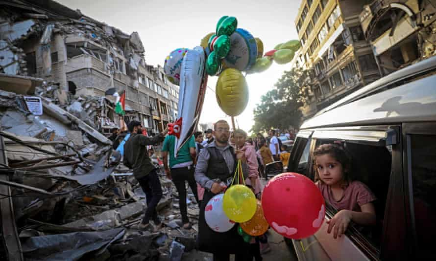 A Palestinian man sells balloons in front of the destroyed al-Shuruq building.