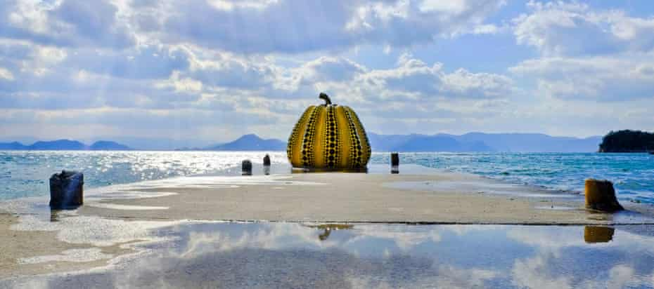 The iconic giant pumpkin by Yayoi Kusama, a surreal beacon jutting out into the sea.