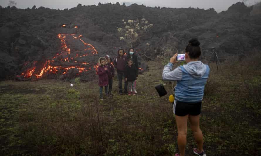 Los miembros de la familia posan para fotos cerca de la lava que fluye del volcán Pacaya cerca de la aldea El Patrocinio.