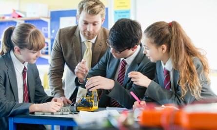 Teacher guiding students assembling robot in science class