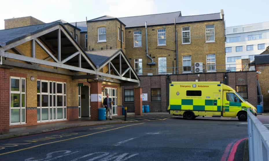 The entrance to a hospital with an ambulance parked outside
