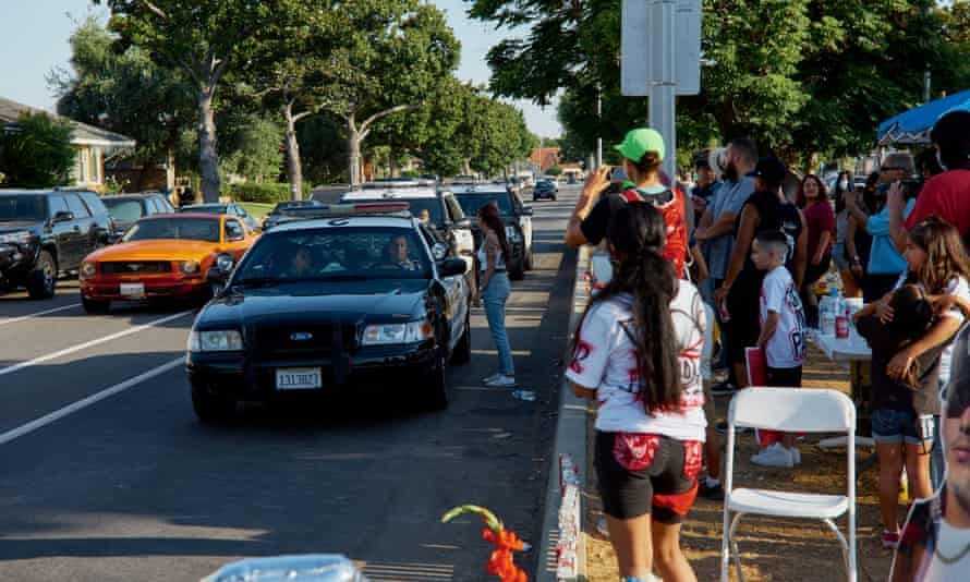 Sheriff's deputies drive by a vigil for Paul Rea in East Los Angeles on 27 June 2020.