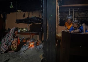 Aunt tending to pot on fire as girls read