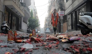 An Indian girl passing the street littered with spent crackers at day after the Diwali in New Delhi.