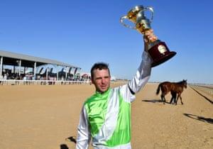 Fast Fella's jockey Adrian Comme celebrates winning the Birdsville Cup