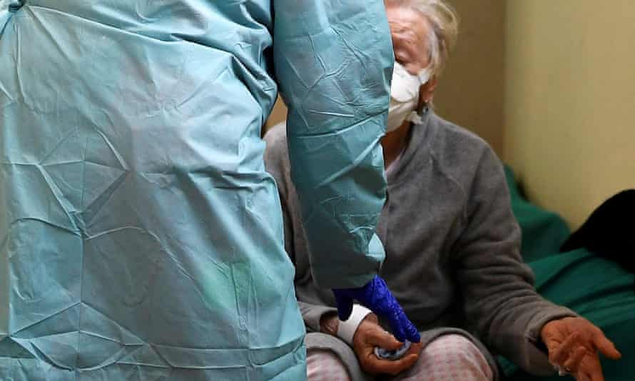 A patient wearing a protective face mask is helped by medical personnel inside the Spedali Civili hospital in Brescia, Italy, on March 13.