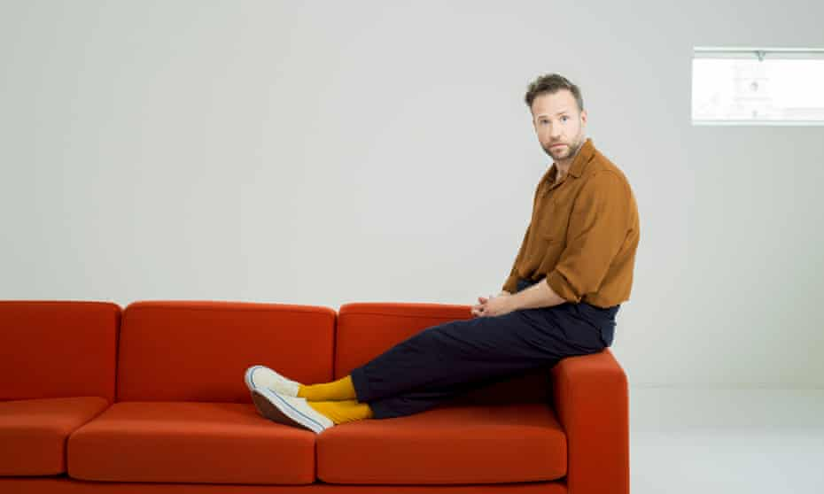 Rafe Spall studio shot, sitting on the arm of a red sofa, his feet on the seat