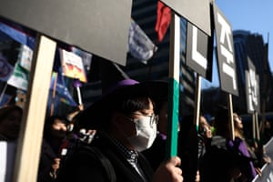 Women wearing witch costumes participate in a march supporting feminism in Seoul, South Korea