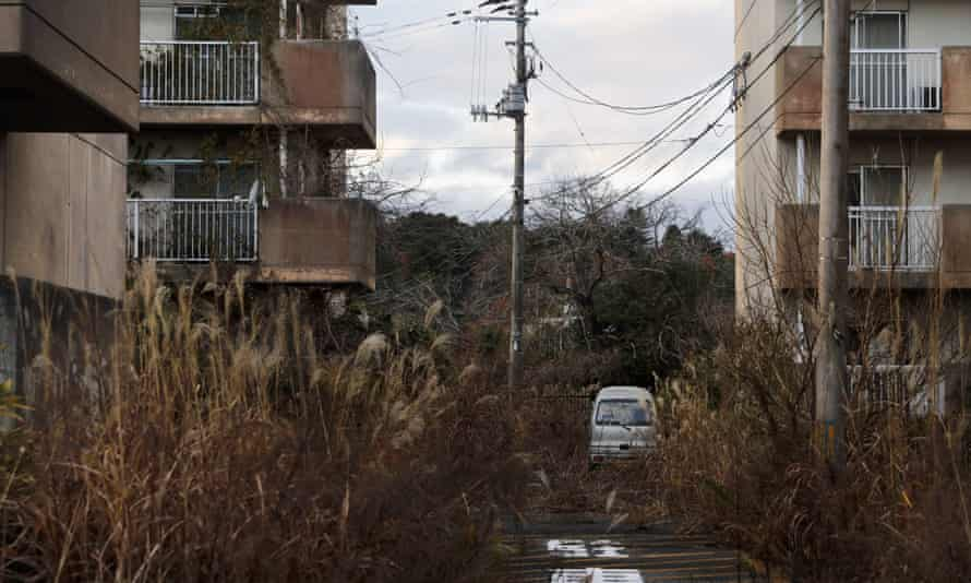 Weeds grow in an abandoned apartment complex in Futaba, Fukushima prefecture, Japan