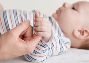 Close up of baby holding mother's hand