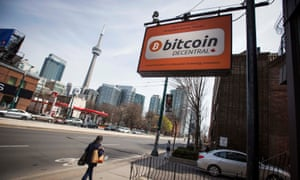 People walk by a 'Bitcoin Decentral' sign for a co-working space in Toronto