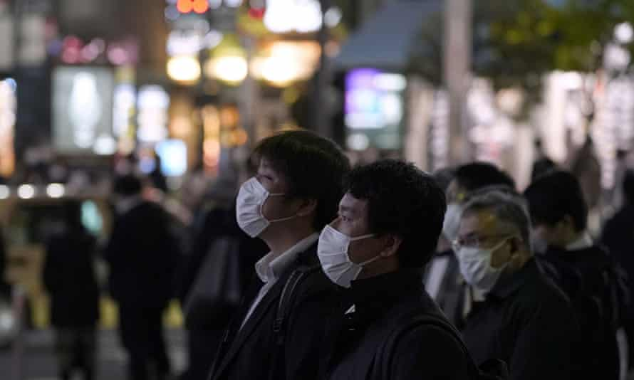 Tokyo pedestrians watch a large screen showing Japan's PM declaring a state of emergency.