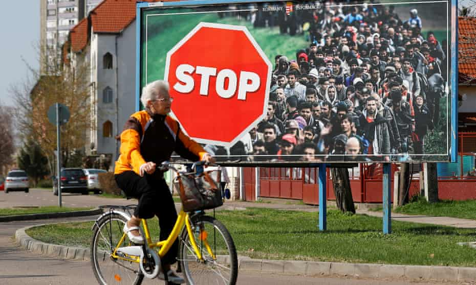 A woman cycles past an anti-immigration election poster for Victor Orbán's Fidesz party before April's election.