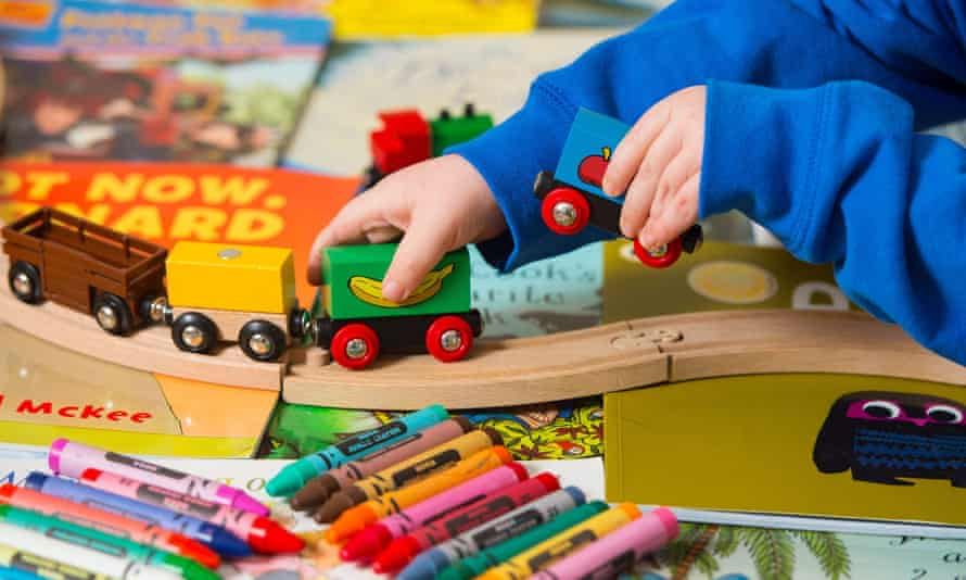 A child playing with a train set and crayons
