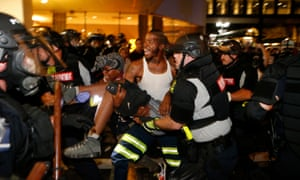 Police and protesters carry a seriously wounded protester into the parking area of the the Omni Hotel during a march to protest the death of Keith Scott.