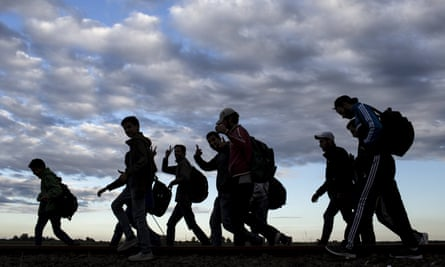 Migrants walk along rail tracks to a collection point in  Hungary