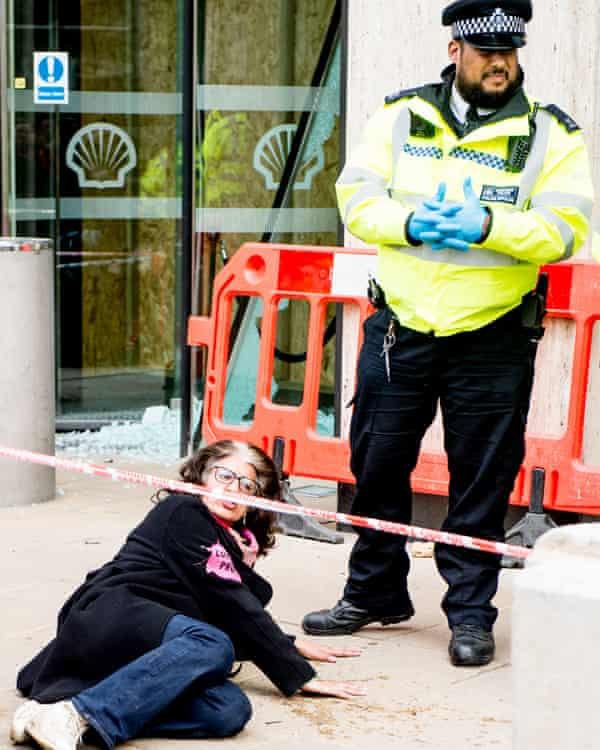 Farhana Yamin glues her hands to the pavement outside the Shell building in London.