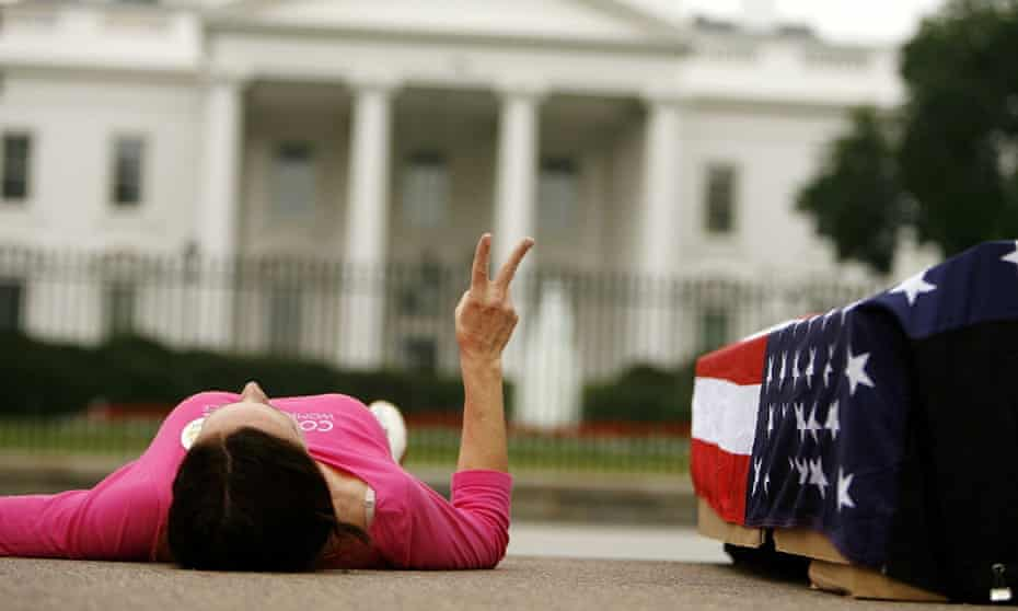 An anti-war protester lays next to a flag-draped mock casket outside the White House in 2016.