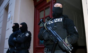 Armed German police stand guard outside a house during a raid.