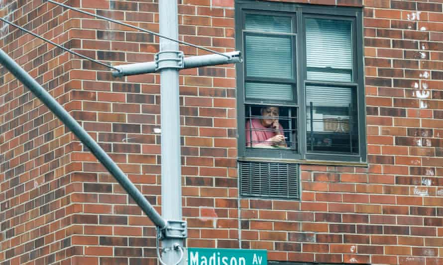 A woman leans out of her window to smoke in New York earlier this month.