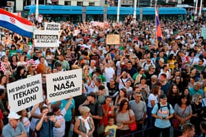 People hold placards as several thousand people protest against measures imposed by the authorities due to the coronavirus pandemic in Zagreb's main square on 5 September 2020.