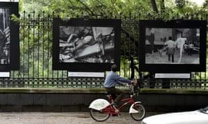 Un ciclista mira unas fotografías del terremoto de 1985, exhibidas en una reja en el parquet de Chapultepec, Ciudad de México.