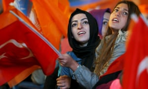 Women wave flags outside the AK party headquarters in Ankara, Turkey