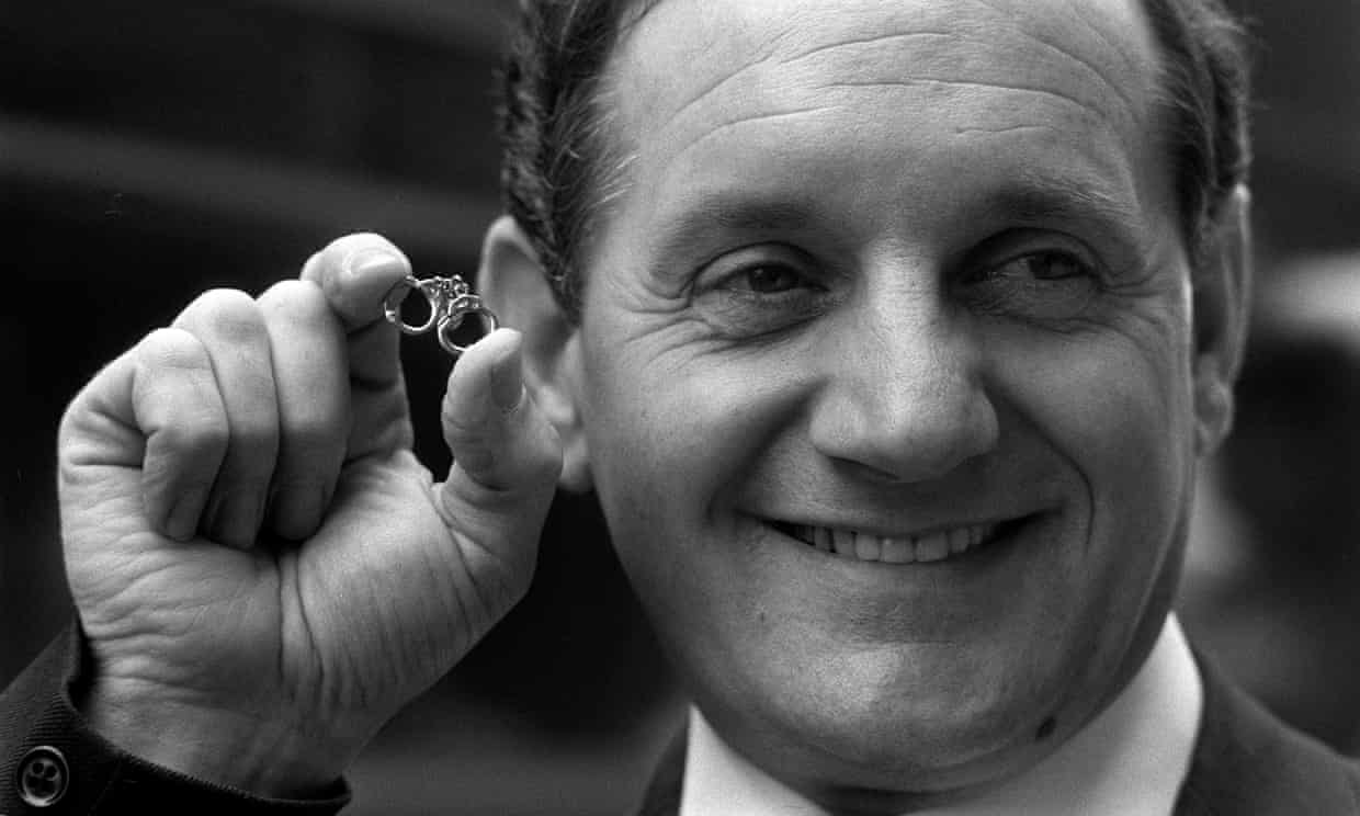 Leonard Read holding a miniature handcuffs tie clip at the Home Office in London in 1972.