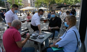 People wearing masks sit at a terrace bar at in Las Ramblas in Barcelona.