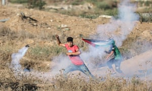 A Palestinian demonstrator throws teargas canisters back at Israeli security forces last month.