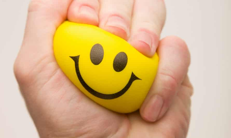 Yellow happy face squeezed by a hand