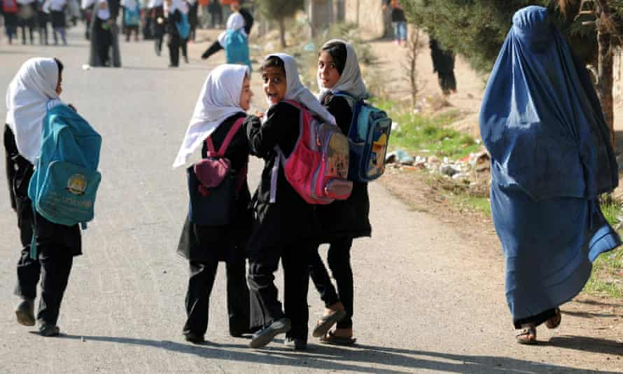 A group of school girls pass a woman wearing a burka in Afghanistan.