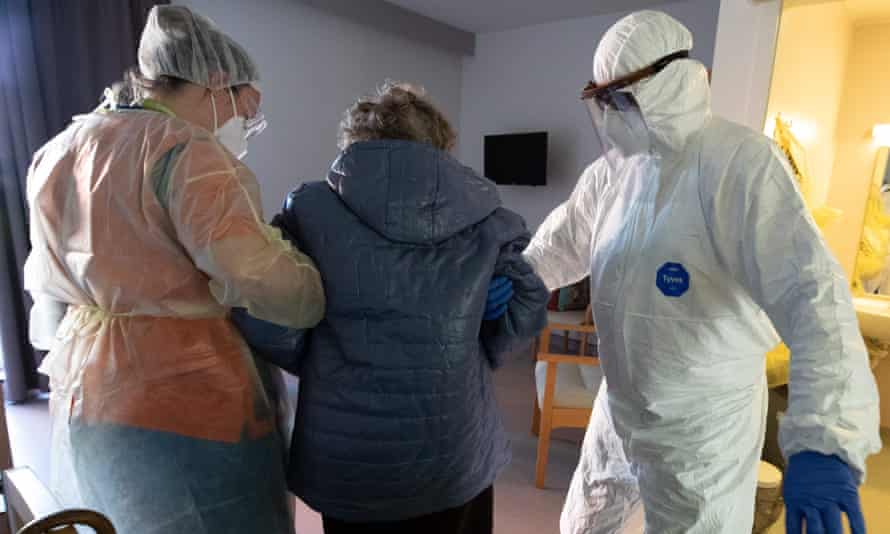 Retirement home's staff, wearing protective clothes and masks, take care of a resident.