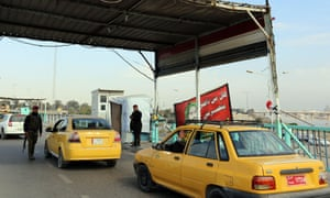 Iraqi security forces inspect a car at a checkpoint near Dora, Baghdad