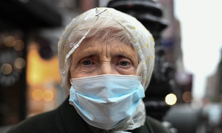 An older woman wears a mask as she comes outside for the nightly 7pm clapping for essential workers in New York City last month.