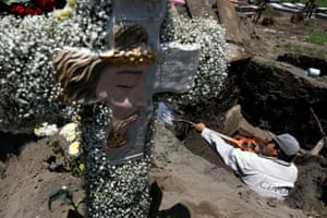 A cemetery worker digs the grave for the burial of a man who died of coronavirus diseas at the San Lorenzo Tezonco cemetery in Mexico City.